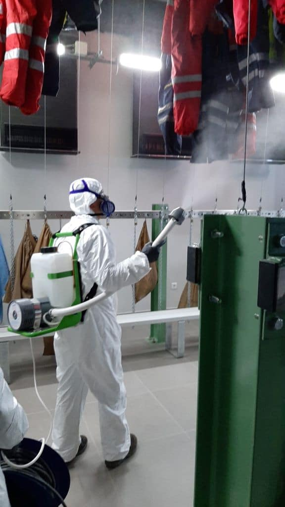 Employee spraying disinfectant